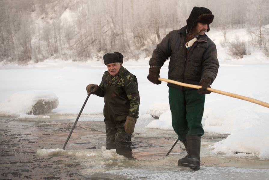 Дедушка и дядька Санька выдалбливают лед для установки вьюнниц